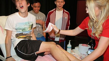 LET'S DANCE: Student Leon Fordyce endures a leg waxing, watched by fellow volunteers (from left) Luk