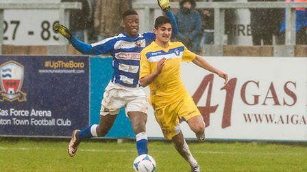Harry Kyprianou of Lowestoft Town pushes forward ahead of Vamara Sanogo of Nuneaton Town during the