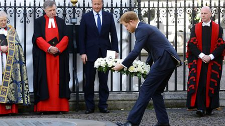 Prince Harry lays a wreath on behalf of his grandmother the Queen, watched by Prime Minister David C