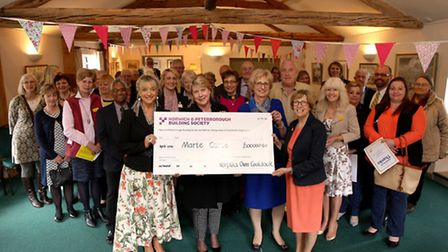 A cheque for £100,000 is handed to Dr Jane Collins, chief executive of Marie Curie (right), by (from