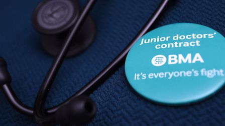 A doctor wears a badge next to her stethoscope in support of the Junior Doctor's contract.