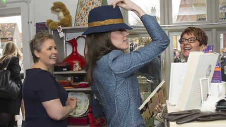The Duchess of Cambridge tries on a hat during her visit to open a new charity shop for East Anglia'