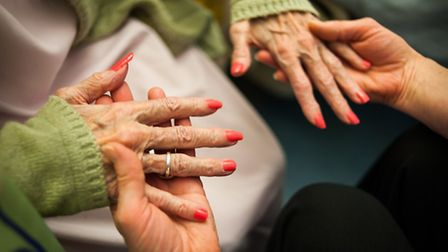 Helping hands. Dementia care worker giving a patient a manicure at the Norfolk & Norwich university