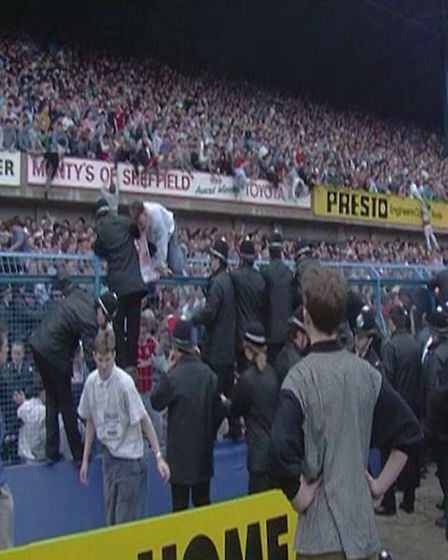 A still from a video of people climbing over the fence at the Leppings Lane end of Hillsborough Stad