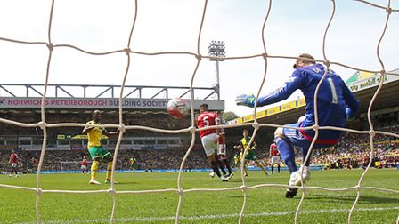 Norwich City striker Cameron Jerome heads at Manchester United goalkeeper David De Gea. Picture by P