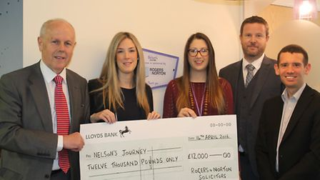 Staff from Rogers and Norton present a cheque to Nelson's Journey charity after a fundraising ball.