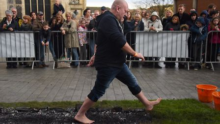 One of the participants strides out across the hot coals during the fire walk in aid of the Big C. P