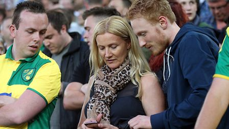 Norwich fans look tense and check their phones as news comes through that Sunderland are winning dur