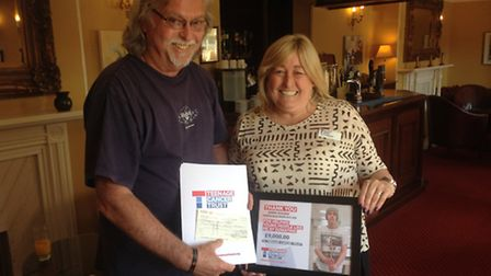 Barry Holden, organiser of North Walsham Live Aid, hands over a cheque for £9,000 to Judith Anderson
