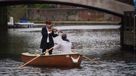 Sianned Jones plays her violin as she is rowed along the river near Fye Bridge as part of the Voice