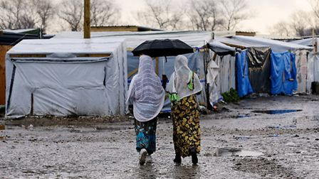 File photo dated 24/02/16 of women walking through the jungle camp in Calais, France, as new researc