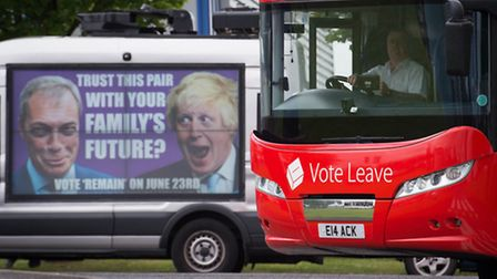 The Vote Leave campaign bus passes a Vote Remain poster featuring Nigel Farage and Boris Johnson. Ph