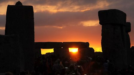 The sun rises above the horizon at Stonehenge in Wiltshire as thousands of people descended on the s