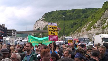 People chanting and holding signs at an impromptu rally in Dover, Kent, as an aid convoy made up of