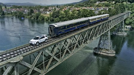 A standard Land Rover Discovery Sport pulling three train carriages, weighing more than 100 tonnes,