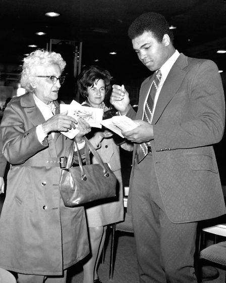 American boxer, Muhammad Ali gives autographs to fans at Heathrow Airport, before flying out to Saud