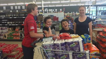 The De Grandis family buy extra supplies for the refugee camp at a local store.
