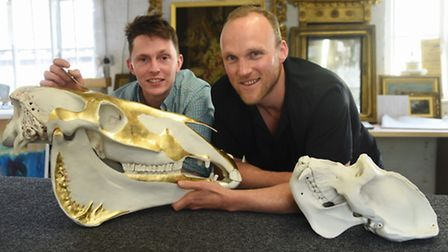 Artist James Webster, right, with a couple of the porcelain animal skulls he has created, a horse an