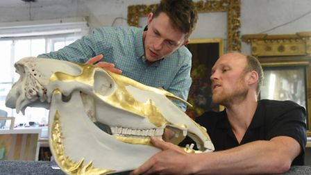 Artist James Webster, right, with one of the porcelain animal skulls he has created, a horse skull,
