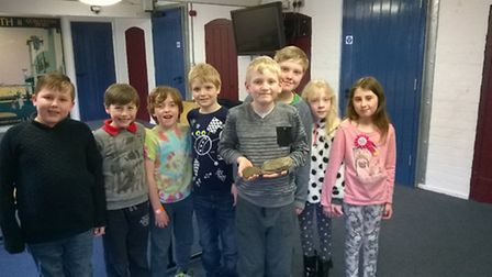 Noah Laws proudly shows off his mammoth tooth with other members of the archaeology group.
