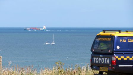 Coastguards keep watch as the cruiser pilot, aided by a yacht, tries to free his craft from the buoy