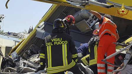 Italian firefighters Vigili del Fuoco inspect the wreckage of two commuter trains after their head-o