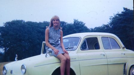 Sally Palmer, whose first car was a Renault Dauphine, sitting on her dad's Dauphine.