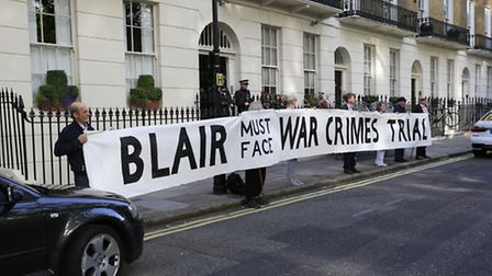 Protesters hold a banner outside the London home of former Prime Minister Tony Blair ahead of the pu