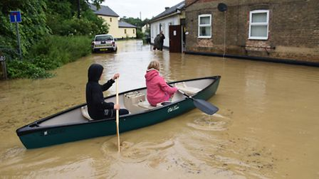 Residents in a canoe on the flooded Low Road at Scole. Picture: DENISE BRADLEY