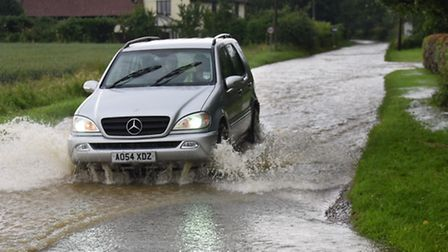 Traffic drives through flood water at Winfarthing on the B1077 which closed off the village. Picture