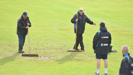 Lowestoft Town ground staff try to deal with the torrential downpours that led to the cancellation o