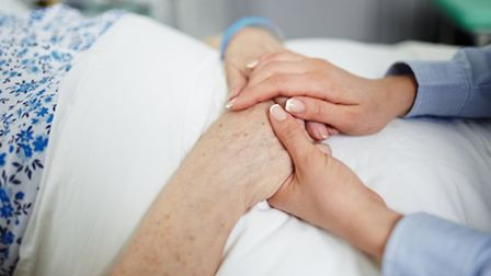 Carer holding hands of senior woman. Photo: Getty Images