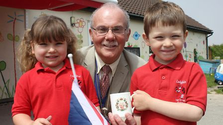 Sheringham toy shop owner Barry Starling handing a mug commemorating the Queen's 90th birthday to fo