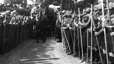 The sea scouts funeral procession approaches Carlton Colville St Peters Church with the route lined