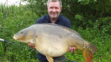 Paul Hatch shows off a magnificent 40lb 5oz mirror carp which he calls Bonnie caught from Billingf