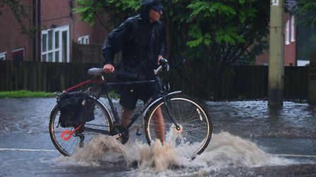 A lone cyclist stands over a blown manhole on Yarmouth Road, Thorpe to protect the traffic as flash