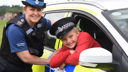 The Mile Cross Community Festival. Matas Salomskas, seven, joins the police for a few minutes, with
