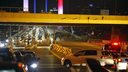 Turkish soldiers block Istanbul's iconic Bosporus Bridge on Friday, July 15, 2016, lit in the colour