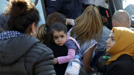 Syrian families embark a bus, transferring them to the western coastal Greek town of Kyllini, from