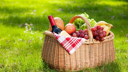 Picnic basket with food on green grass. Photo: Getty Images/iStockphoto