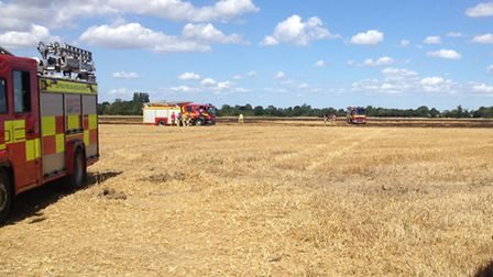 Firefighters working on the scene of the field fire at Bedingfield Hall Farms