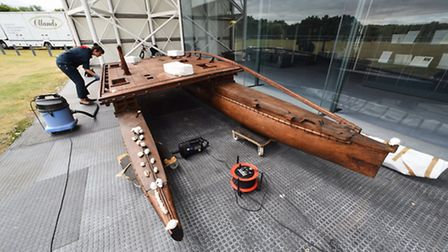 A traditional Fijian double hull canoe being meticulously cleaned before it is installed inside the