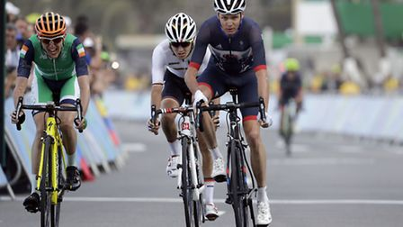 Christopher Froome of Great Britain, right, rides to cross the finish line of the men's cycling road