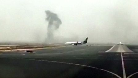 This image made from video shows smoke rising after an Emirates flight crash landed at Dubai Interna