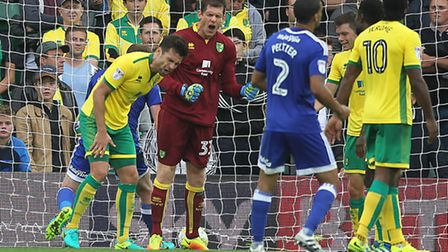 Russell Martin and Michael McGovern react after former Norwich player Anthony Pilkington scores Card