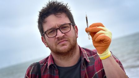 TV biologist Ben Garrod taking part in Great Yarmouth charity beach clean. Pictured with a syringe t