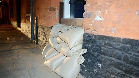 Flashback to 2103. Flood waters start to rise in King's Lynn - Boards and sandbags in front of a doo