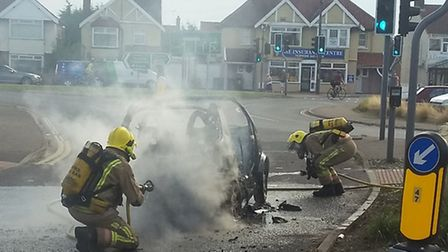 Firefighters extinguish the car fire. Picture: James Field @Jimbob_Field