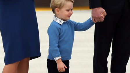 Prince George stands between his parents the Duke and Duchess of Cambridge as the Royal Party, inclu