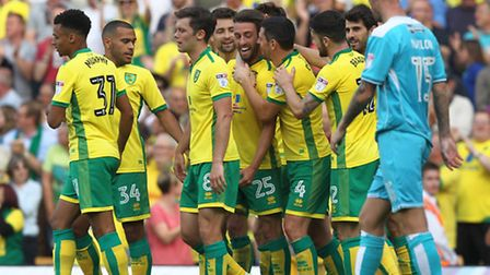 Ivo Pinto is mobbed by his Norwich City team mates after sealing a 3-1 Championship win against Burt